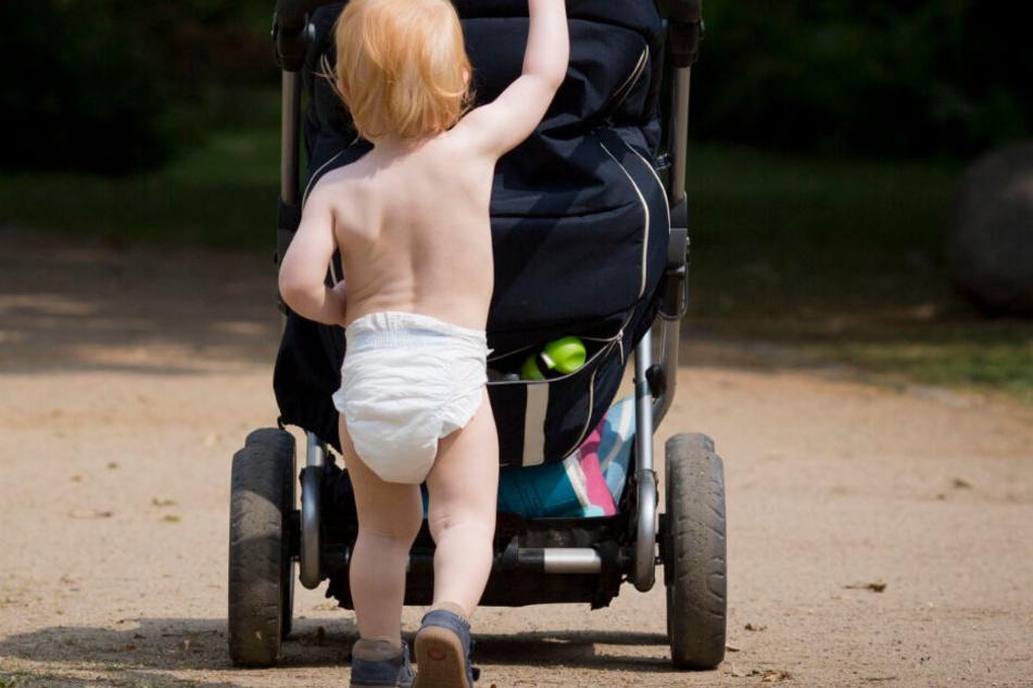 Ein nur mit einer Windel bekleidetes Kind schiebt einen Kinderwagen.