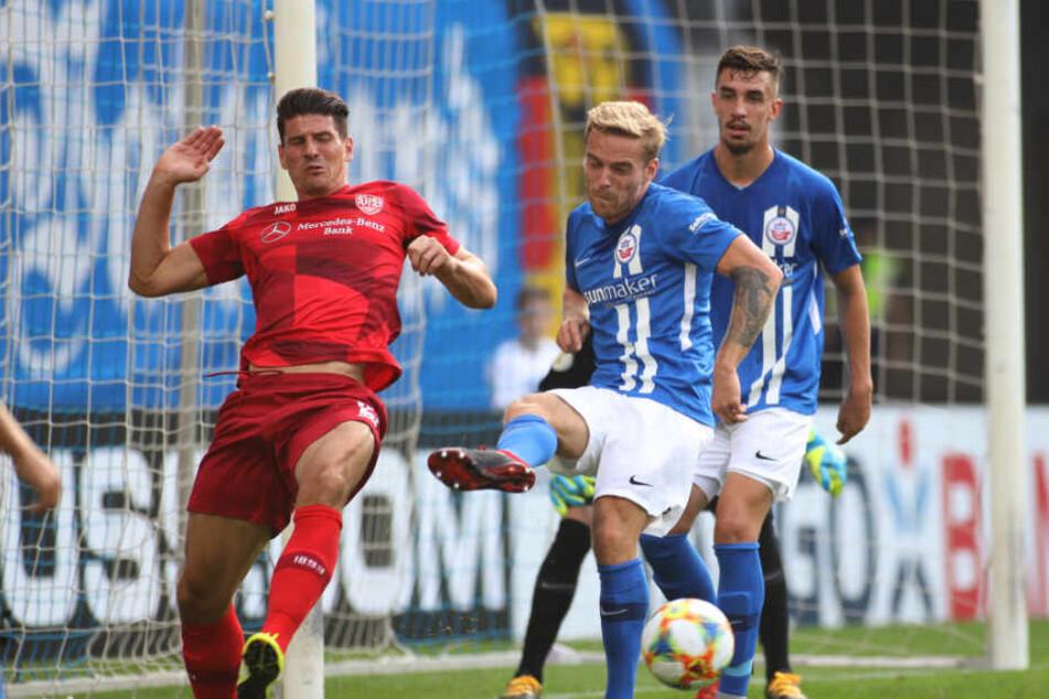 Rostocks Nils Butzen (M) kämpft mit Stuttgarts Mario Gomez (l) um den Ball.