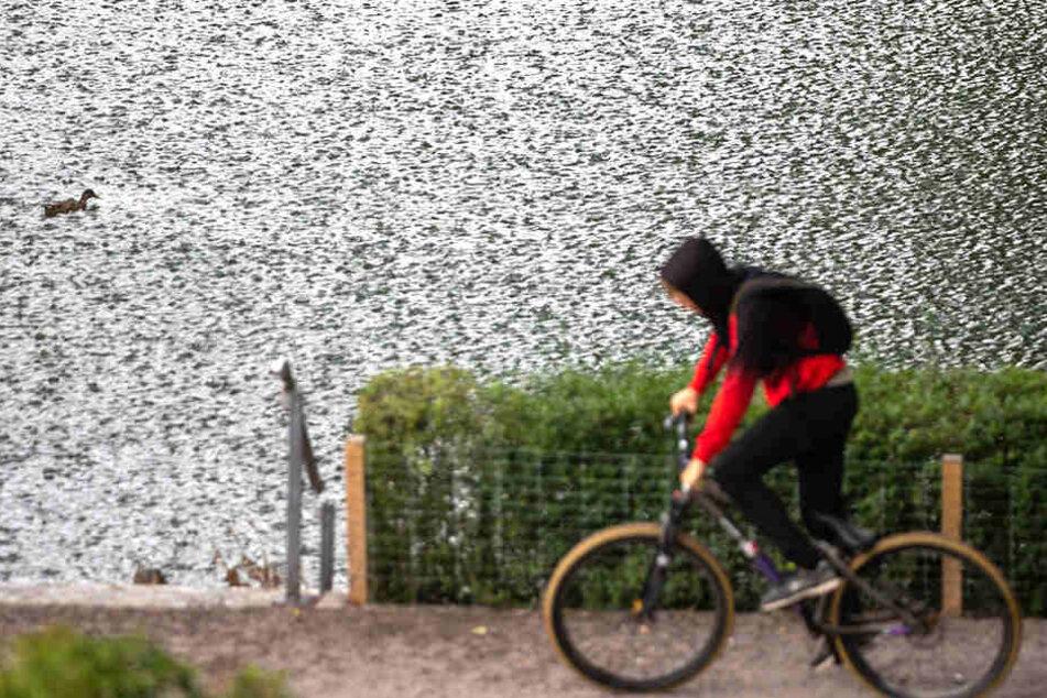 Ein Fahrradfahrer vor einer spätsommerlichen Regenwand in Thüringen.