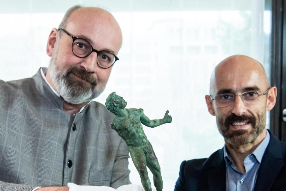 Martin Maischberger (r), stellvertretender Direktor der Antikensammlung der Staatlichen Museen zu Berlin, übergibt Martin Eberle, Direktor der Museumslandschaft Hessen Kassel, die Bronzestatuette.