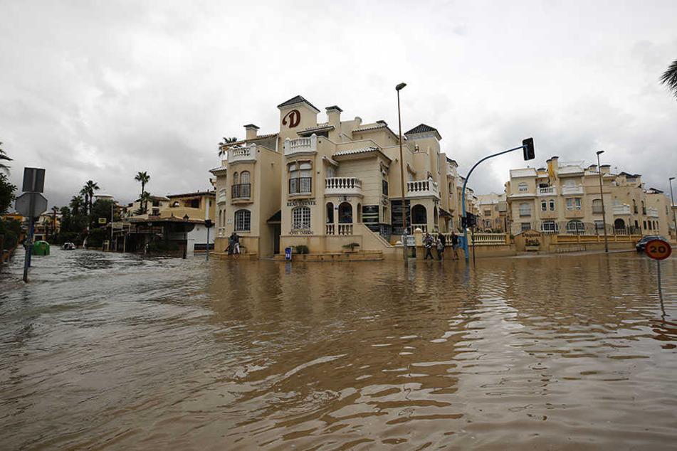 Menschen gehen nach Unwettern und Regenfällen eine überflutete Straße von Torrevieja entlang.
