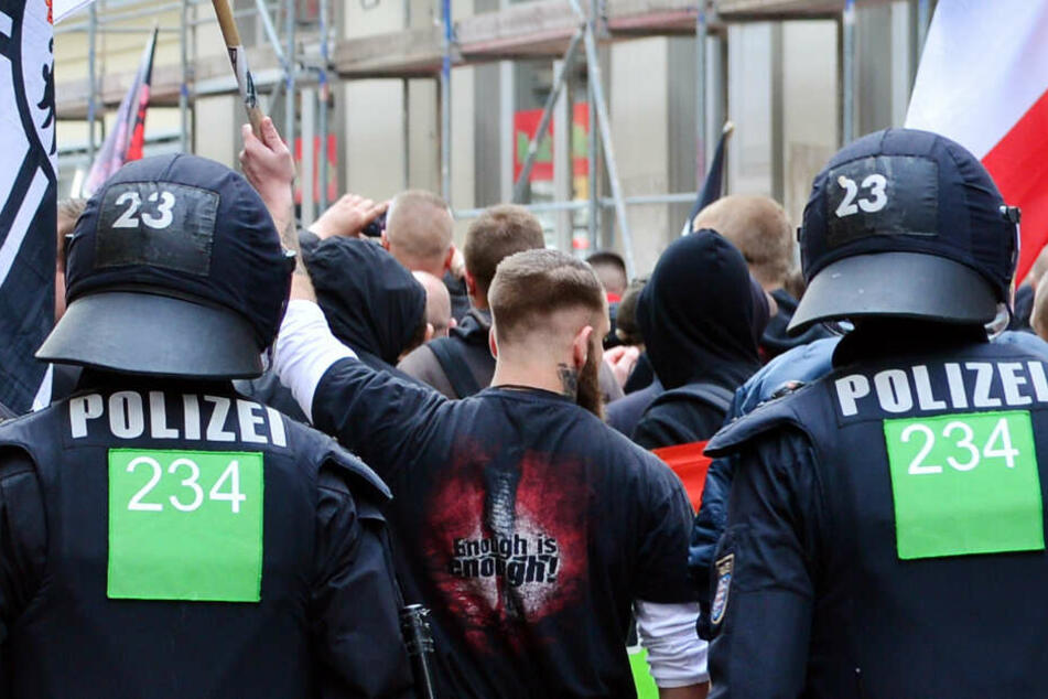 """Teilnehmer einer Demonstration der Partei """"Die Rechte"""" laufen am 01.05.2016 in Erfurt (Thüringen) durch die Stadt und werden von Polizisten eskortiert. (Archivbild)"""