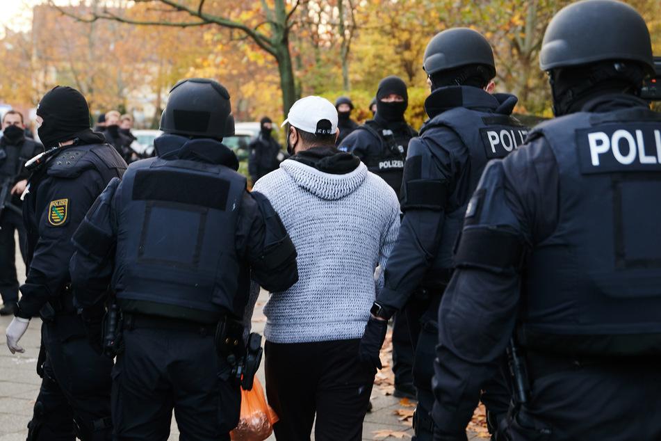 Beamte der Polizei bringen bei einem Einsatz eine Person zur Identitätsprüfung.