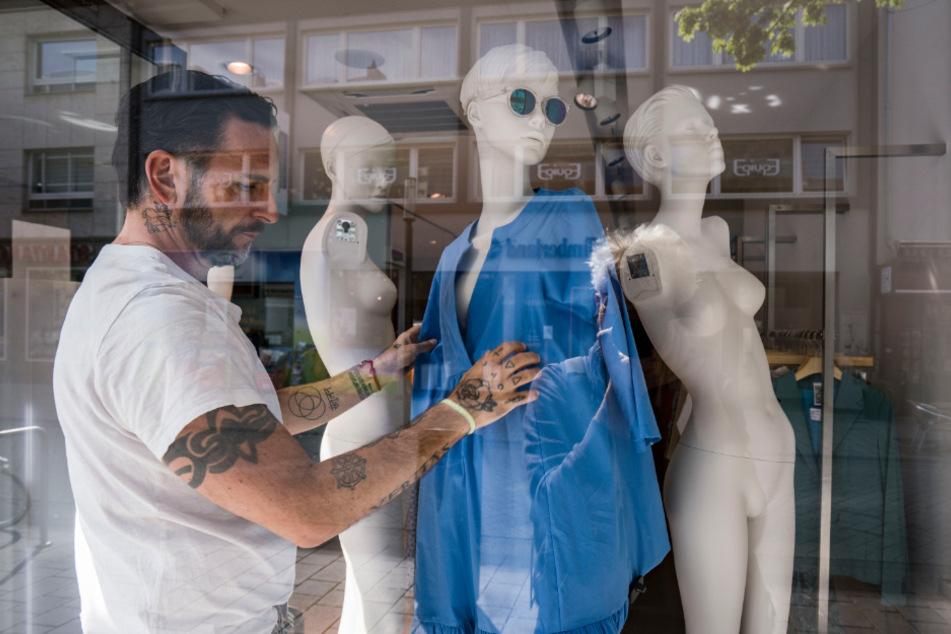 Ein Dekorateur bekleidet eine Schaufensterpuppe.