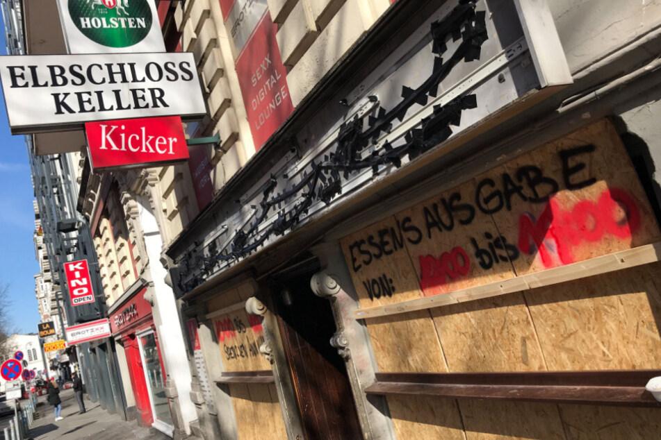 """""""Essensausgabe von 1200 bis 1400"""" steht auf den Holzplatten vor den verbarrikadierten Fenstern der Kultkneipe """"Elbschlosskeller""""."""