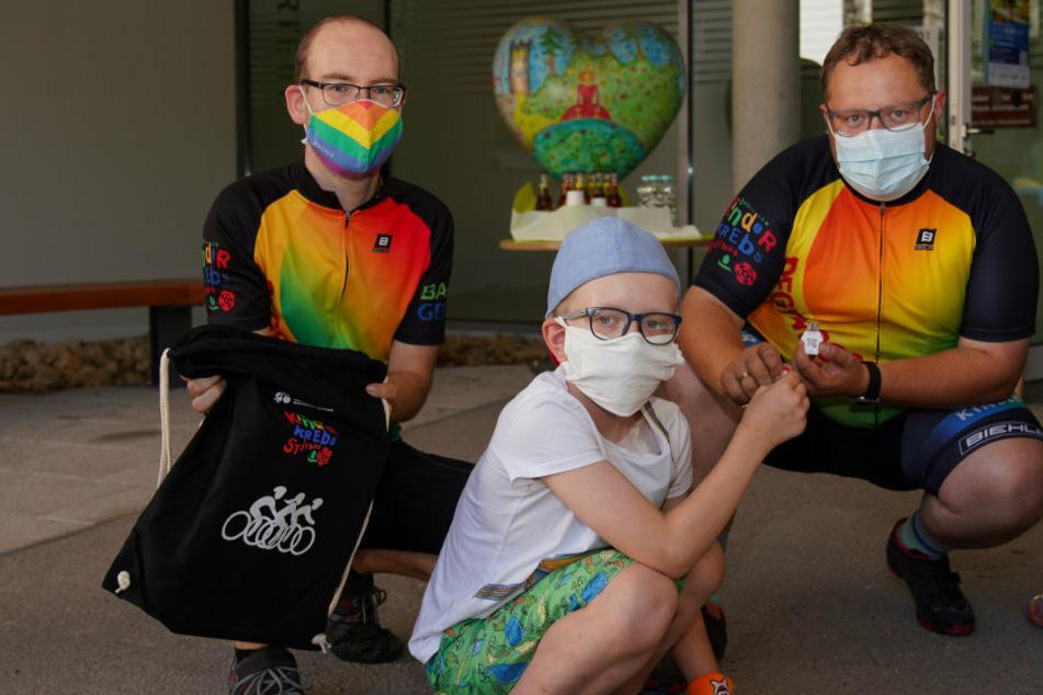 Georg Teucher (31) von der Regenbogenfahrt, Krebspatient Lucas Glowka (10) und Andreas Führlich (35, Sonnenstrahl) bei der Übergabe der Mutperlen. Für die kleinen Patienten ein Highlight im Klinikalltag.