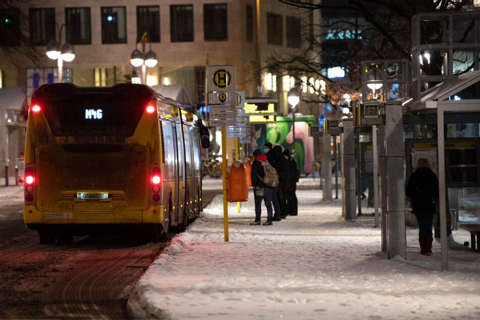 Berlin: Reisende stehen am frühen Morgen am Bahnhof Zoo an einer Bushaltestelle vor einem Bus.