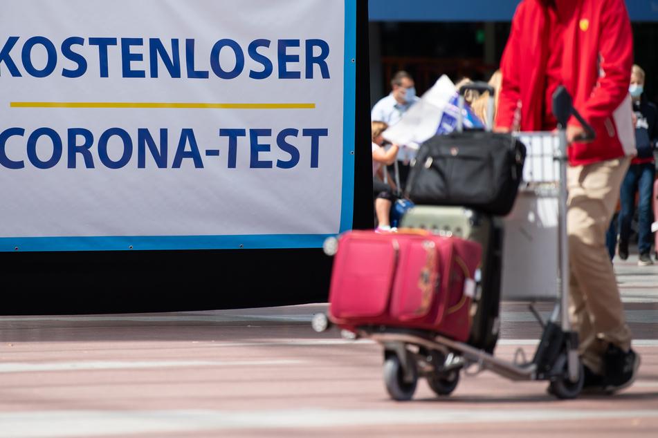 """Flugreisende gehen am Flughafen München an einem Schild mit der Aufschrift """"Kostenloser Corona-Test"""" entlang."""