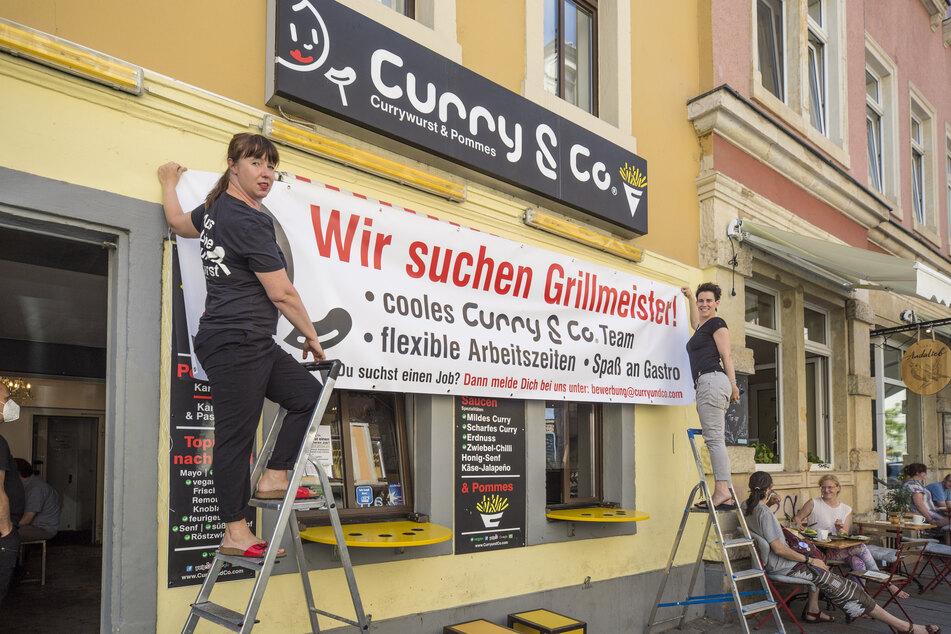 Susanne Meyer-Götz (45, l.) und Simone Meyer-Götz (40) hängen an ihrem Bistro das Banner für die Mitarbeitersuche auf.