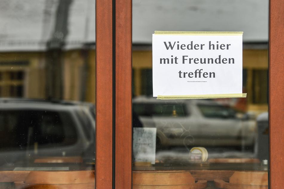 """Am Fenster einer geschlossenen Bar in Friedrichshagen hängt ein Schild mit der Aufschrift """"Wieder hier mit Freunden treffen""""."""