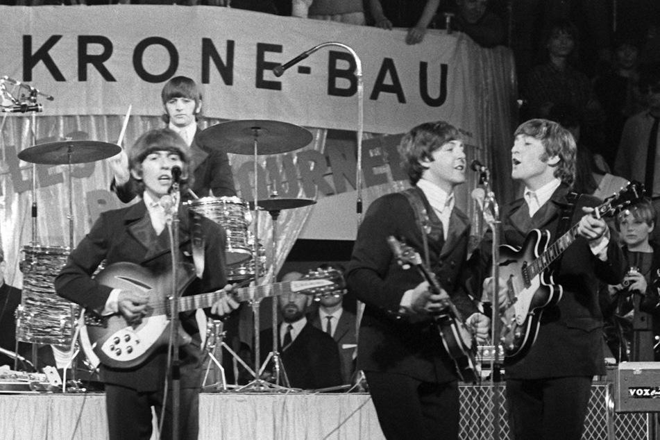 Die Beatles, (v.l.n.r.) George Harrison, Paul McCartney, John Lennon und im Hintergrund am Schlagzeug Ringo Starr, treten im Circus Krone-Bau im Jahr 1966 in München auf.