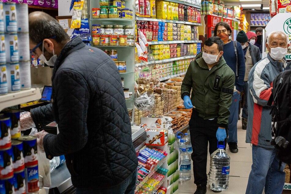 Kunden mit Schutzmasken stehen in einem Supermarkt in Istanbul in der Schlange an der Kasse.