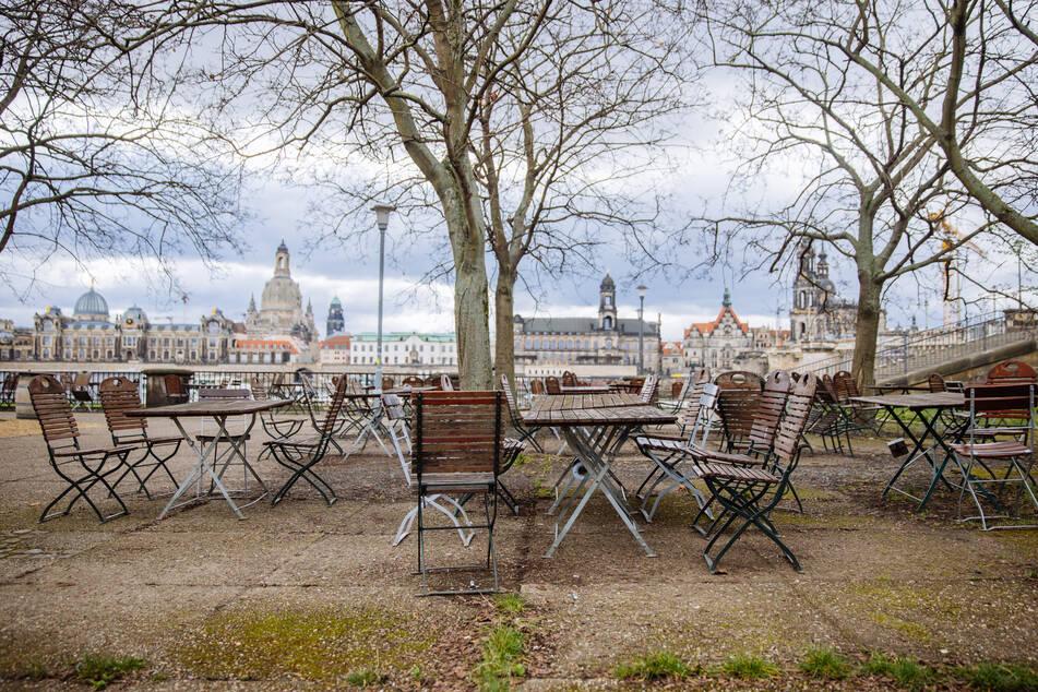 Ein leerer Biergarten gegenüber der historischen Altstadt am Dresdner Elbufer.