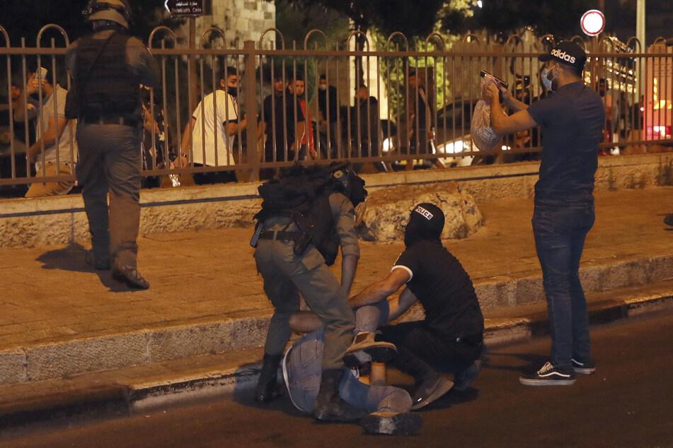 Sicherheitskräfte, sowohl in Uniform als auch in Zivil, verhaften einen palästinensischen Mann in der Nähe des Damaskustors in der Altstadt von Jerusalem während Zusammenstößen zwischen der Polizei und palästinensischen Demonstranten.
