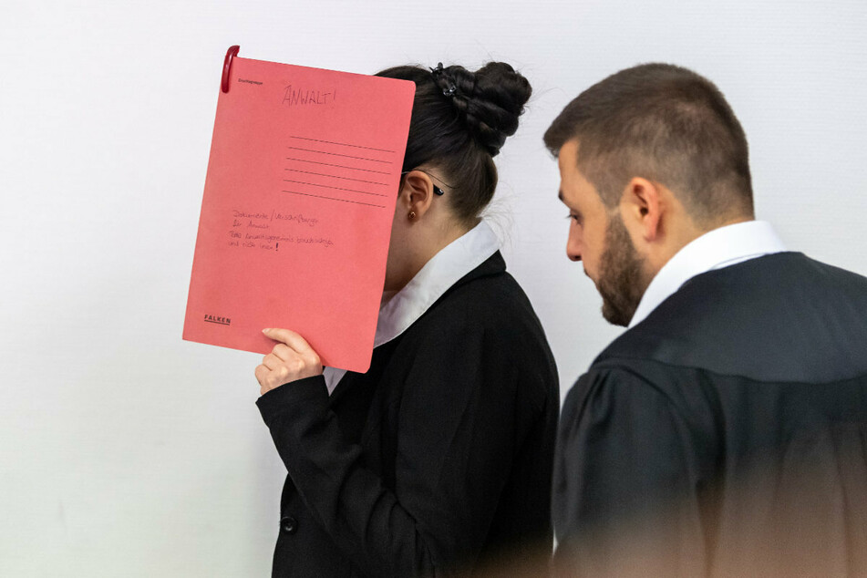 Die Angeklagte Jennifer W., die sich der Terrormiliz Islamischer Staat (IS) im Irak angeschlossen haben soll, hält sich beim Betreten des Gerichtssaals einen roten Aktendeckel vors Gesicht. Rechts steht ihr Anwalt Ali Aydin.
