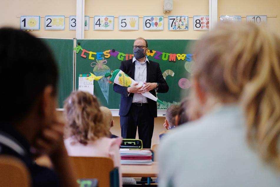 Christian Piewarz (CDU), Bildungsminister des Landes Sachsen, spricht in der Grundschule Beilrode mit einer Zuckertüte in den Händen zu Erstklässlern.