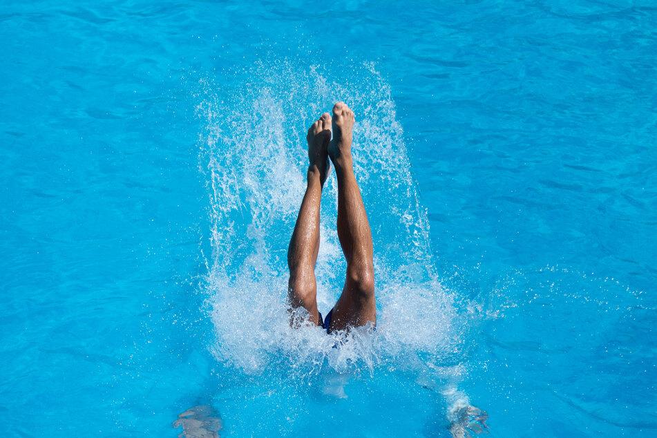 Ein junger Mann landet nach einem Sprung vom Drei-Meter-Brett im Kaifu-Bad im Wasser.