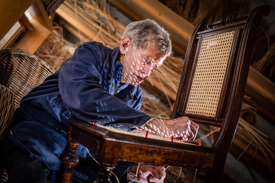 Korb- und Flechtwerkgestalter Günter Jahn (80) arbeitet in seiner Werkstatt an einem Stuhlsitz.
