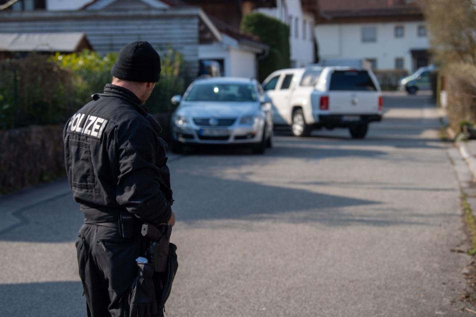 Ein Polizist steht auf einer Straße vor einem Haus in Vogtareuth, in dem drei Tote Menschen aufgefunden worden waren.
