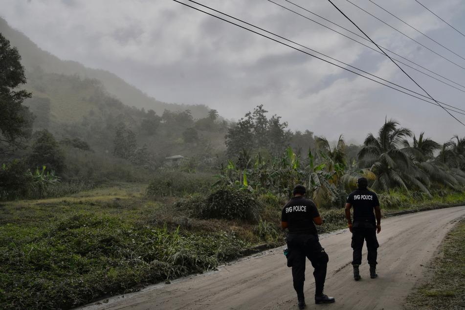 Kingstown: Polizisten patrouillieren nach dem Ausbruch des Vulkans La Soufriere auf einer aschebedeckten Straße, um Menschen davon abzuhalten, sich dem aktiven Vulkan zu nähern.
