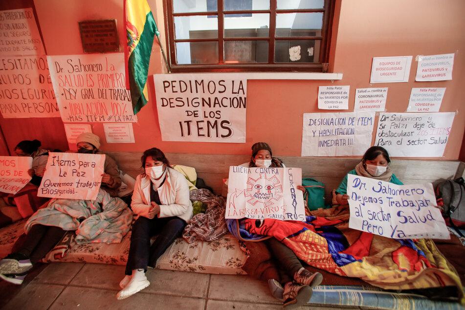 Mitglieder des Gesundheitspersonals mit Mundschutzmasken sitzen auf einer Matratze am Eingang des Allgemeinen Krankenhauses von La Paz und fordern durch einen Hungerstreik mehr Schutzausrüstung inmitten der Corona-Pandemie.