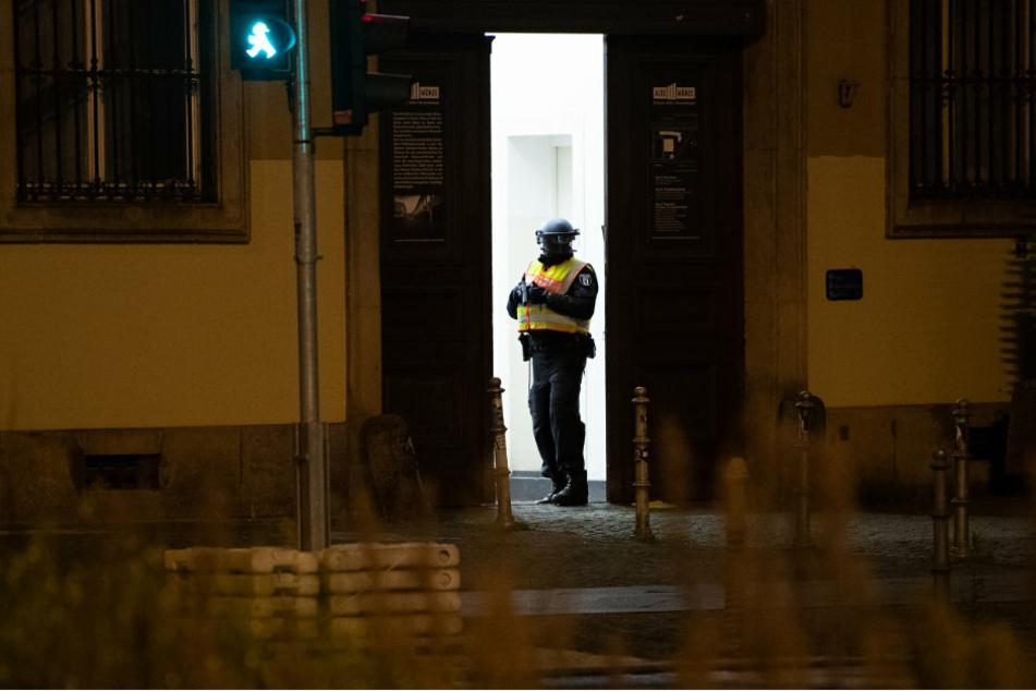 Ein Polizeibeamter steht mit gezogener Waffe im Eingang der Alte Münze in Berlin-Mitte.