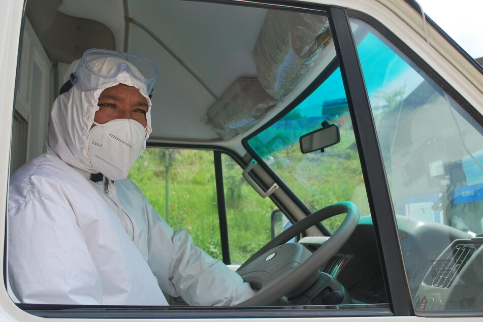Der Nepalese Buddha Krishna Baga Shrestha sitzt mit Mundschutz und Schutzanzug am Steuer eines Krankenwagen.