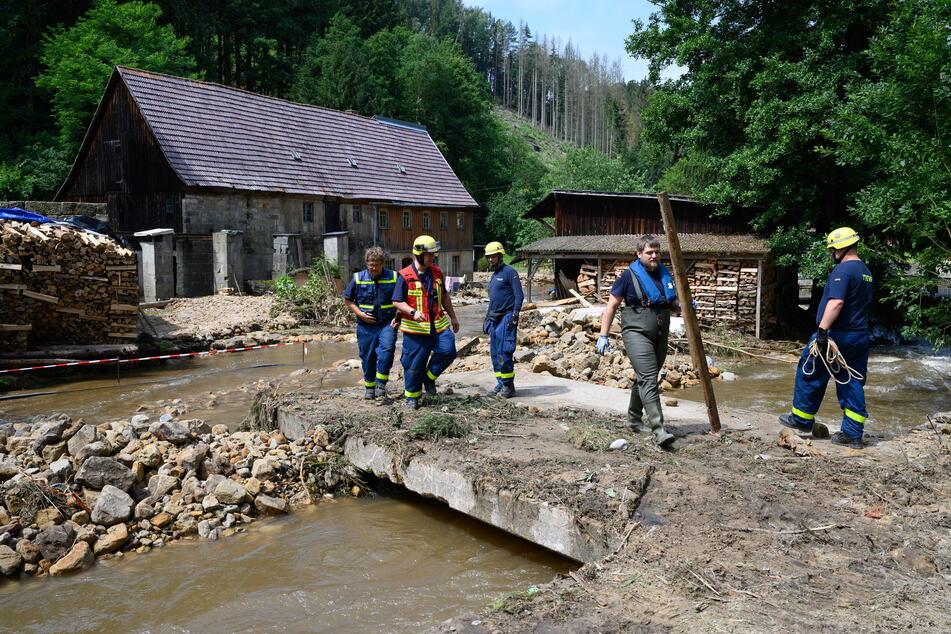 Einsatzkräfte des THW beseitigen am Krippenbach Geröll und begutachten die Schäden.