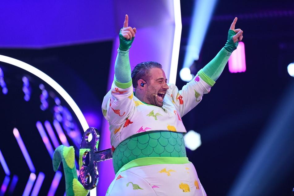"""Sasha (49) hat sich als süßer Dino verkleidet auf Platz 1 von """"The Masked Singer"""" gesungen."""