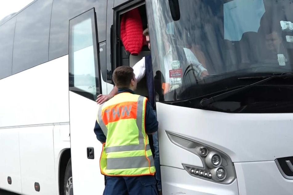 Ein Mitarbeiter des Technischen Hilfswerks an einem Reisebus.