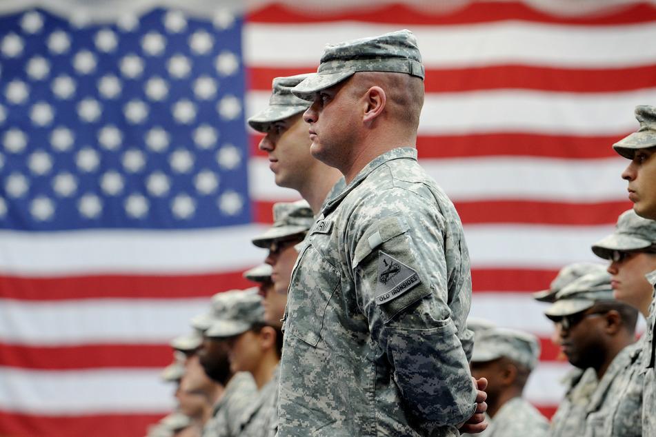 2008, Wiesbaden: US-Soldaten stehen nach ihrer Ankunft auf der US-Airbase in Wiesbaden-Erbenheim vor einer US-Flagge.