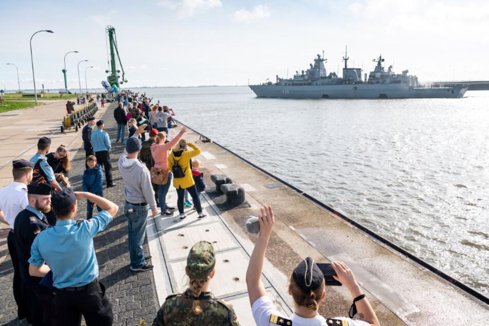 """Angehörige der Besatzungsmitglieder winken zum Abschied der Fregatte """"Brandenburg"""" in Wilhelmshaven."""