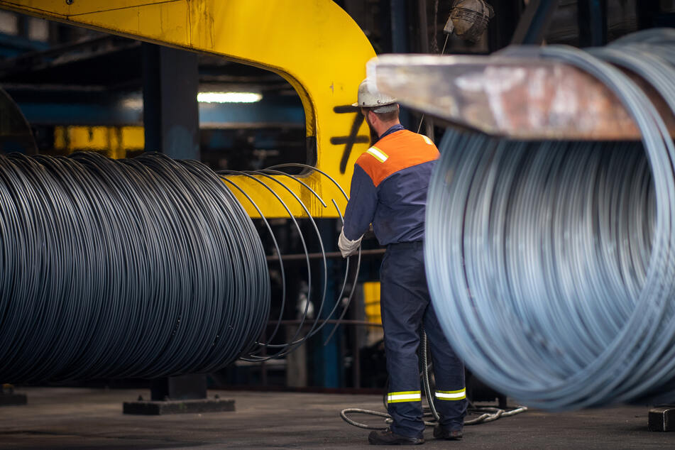 Ein Mitarbeiter arbeitet an einer Produktionslinie für Stahlherstellung.