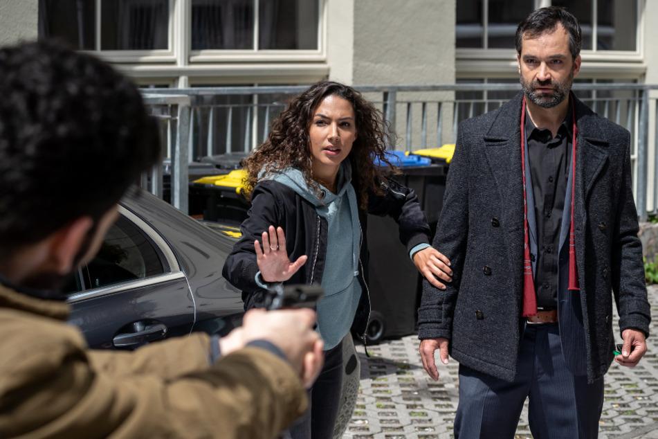 Kim holt ihren Vater von der Arbeit ab, da richtet plötzlich ein Mann eine Waffe auf ihn. Was haben die beiden miteinander zu tun?