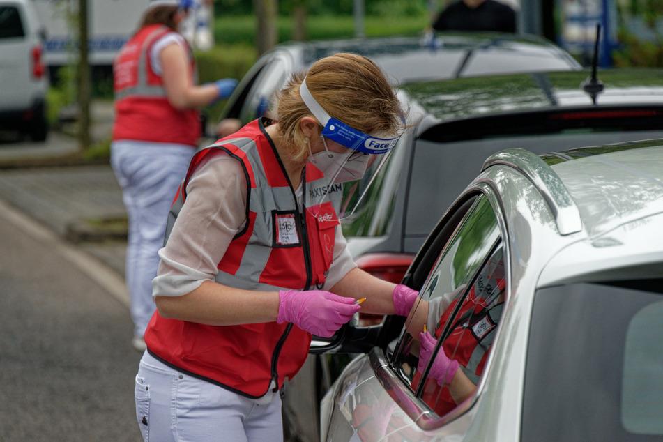 Eine Mitarbeiterin spritzt bei einer Drive-in-Impfaktion in Meerbusch (NRW) eine Dosis Impfstoff in den Arm eines Fahrers, nun läuft das Projekt auch in Berlin an.