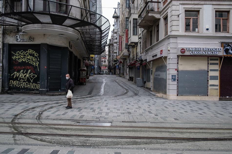 Ein Mann mit Schutzmaske steht in der leeren Istiklal Caddesi (Unabhängigkeitsstraße).