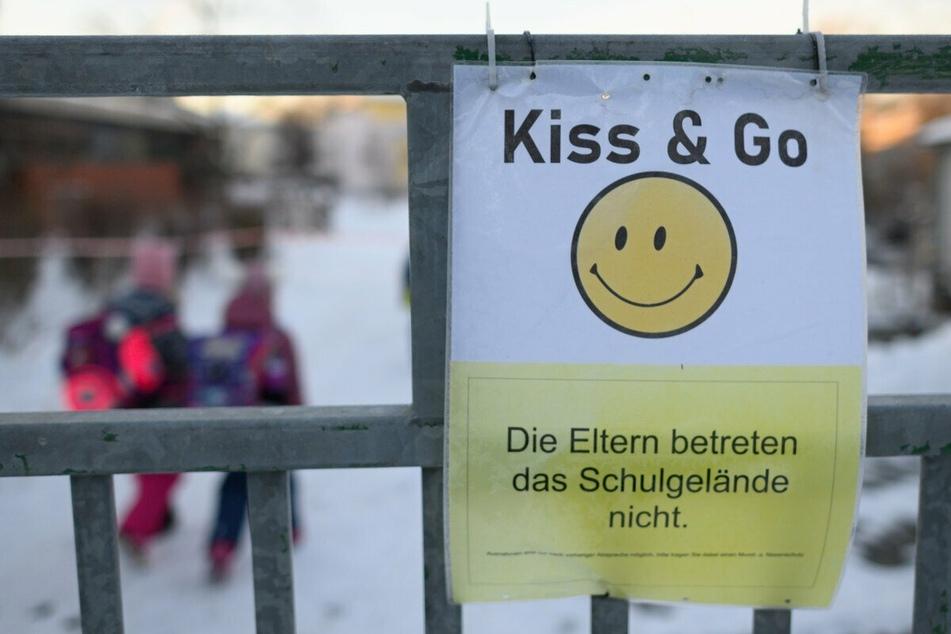 """Ein Schild mit einem Smiley und der Aufschrift """"Die Eltern betreten das Schulgelände nicht"""" hängt am Tor der Regenbogenschule in Dresden."""