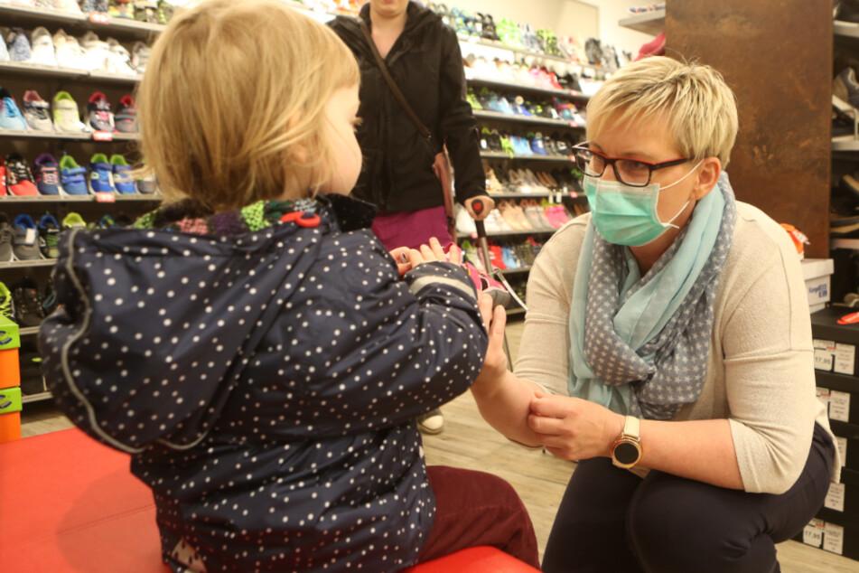In einem Schuhgeschäft in Werningerode bedient eine Verkäuferin mit Mundschutz ein Mädchen. In Sachsen-Anhalt ist dies bereits erlaubt, ab Montag dürfen auch in Bayern viele Geschäfte wieder öffnen.