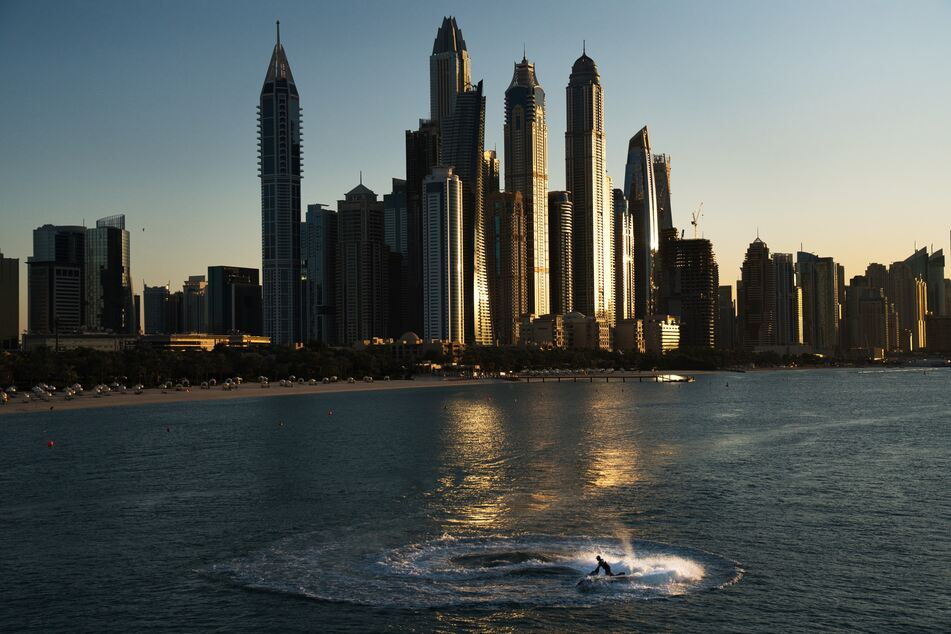 Ein Mann fährt einen Jet-Ski im Sonnenuntergang vor der Küste von Dubai.