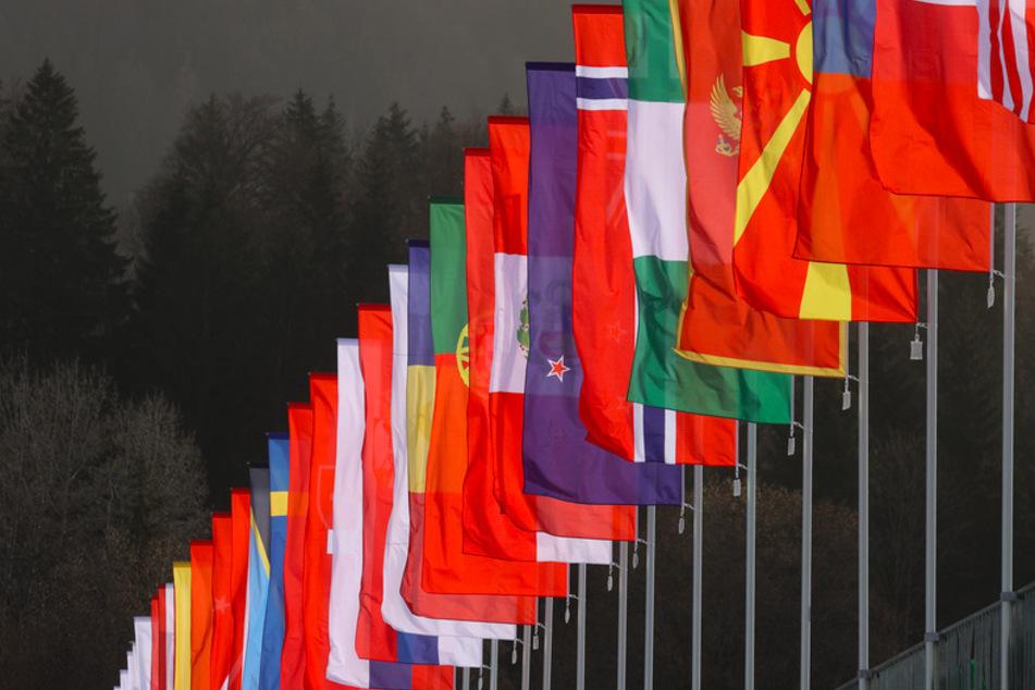 Fahnen verschiedener Nationen säumen die Zuschauertribüne in Oberstdorf.