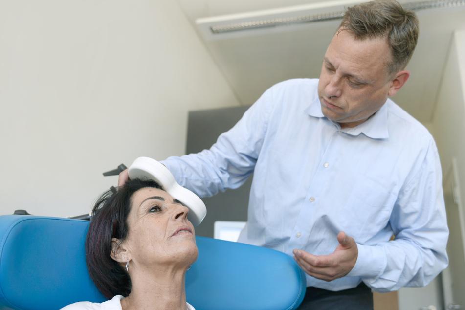 Christian Plewnia, Facharzt für Psychiatrie und Psychotherapie an der Universitätsklinik Tübingen legt der Patientin Erika Fuchs eine Magnetspule an.