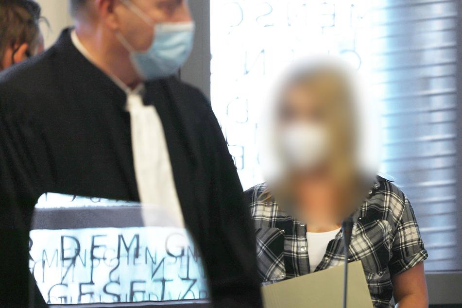 Die angeklagte Mutter (r.) steht neben einem ihrer Anwälte auf der Anklagebank.