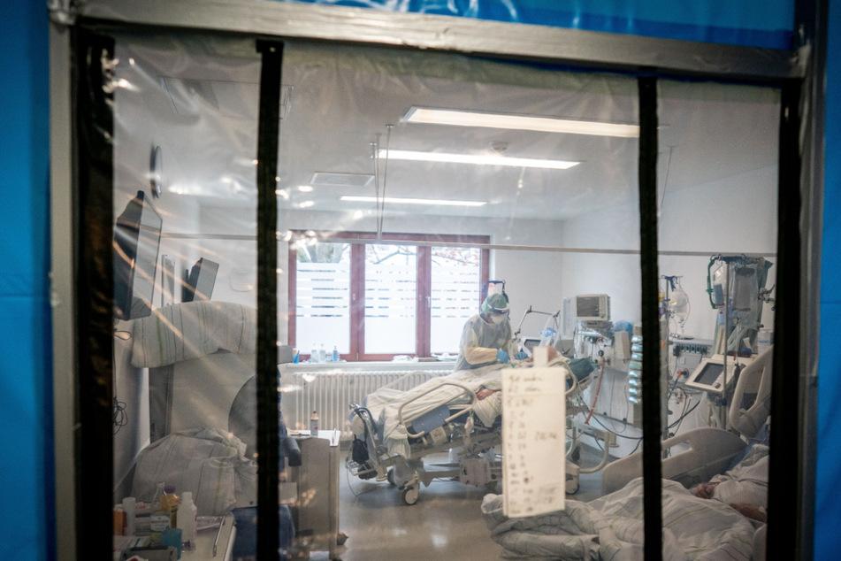 Ein Intensivpfleger betreut hinter einer Schleuse in einer Schutzausrüstung mit Mund-Nasenbedeckung, Gesichtsschutz, Kittel und Haube auf der Intensivstation des Krankenhauses Bethel einen Corona-Patienten.