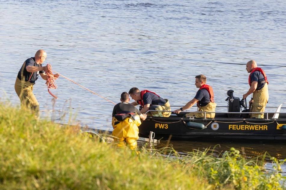 Feuerwehrleute kehren ans Ufer zurück.