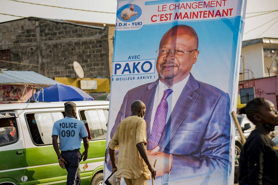 Menschen gehen an einem Wahlplakat des oppositionellen Präsidentschaftskandidaten Guy Brice Parfait Kolelas vorbei.