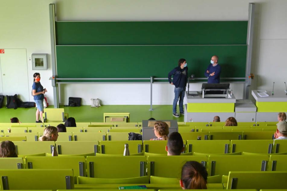 tudierende der Wirtschafts-Wissenschaften sitzen unter Wahrung der Abstandsregel in einem Hörsaal und warten auf den Beginn der Klausur.