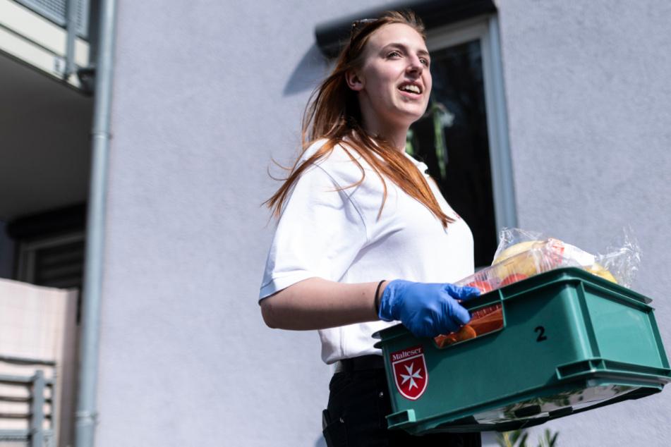 Eine junge Frau verteilt Einkäufe.