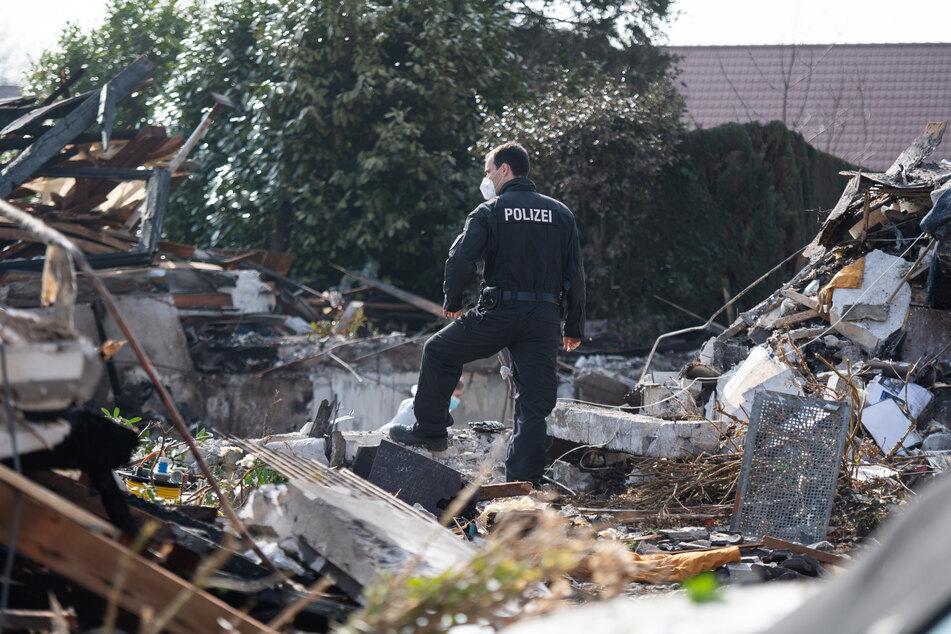 Einsatzkräfte arbeiten in den Überresten des Wohnhauses.