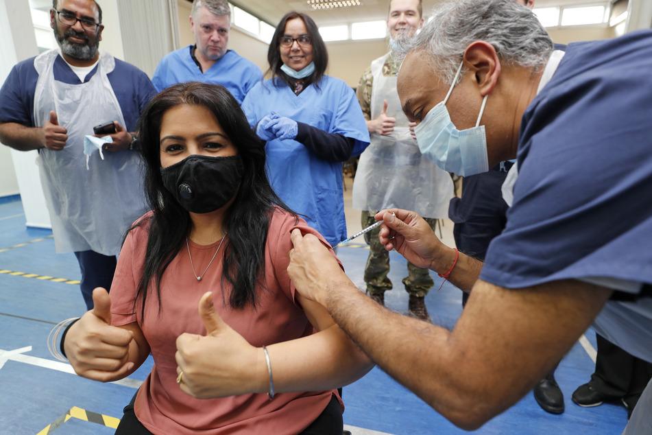 Der Arzt Anil Mehta verabreicht, umgeben von seinem Team aus Doktoren und Arzthelfern, am 28. Februar die 10.000ste Impfung in seiner Praxis in London.