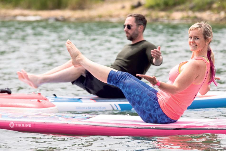 Fitness-Coach Julia macht Wasser-Yoga auf dem Surfbrett